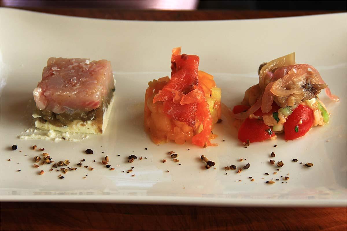 Lantipasto: panzanella con filetto di sardina in saor, battuto di melanzana viola con ricotta di Tremosine e tartara di coregone, composta di melone e sedano bianco con trota affumicata.